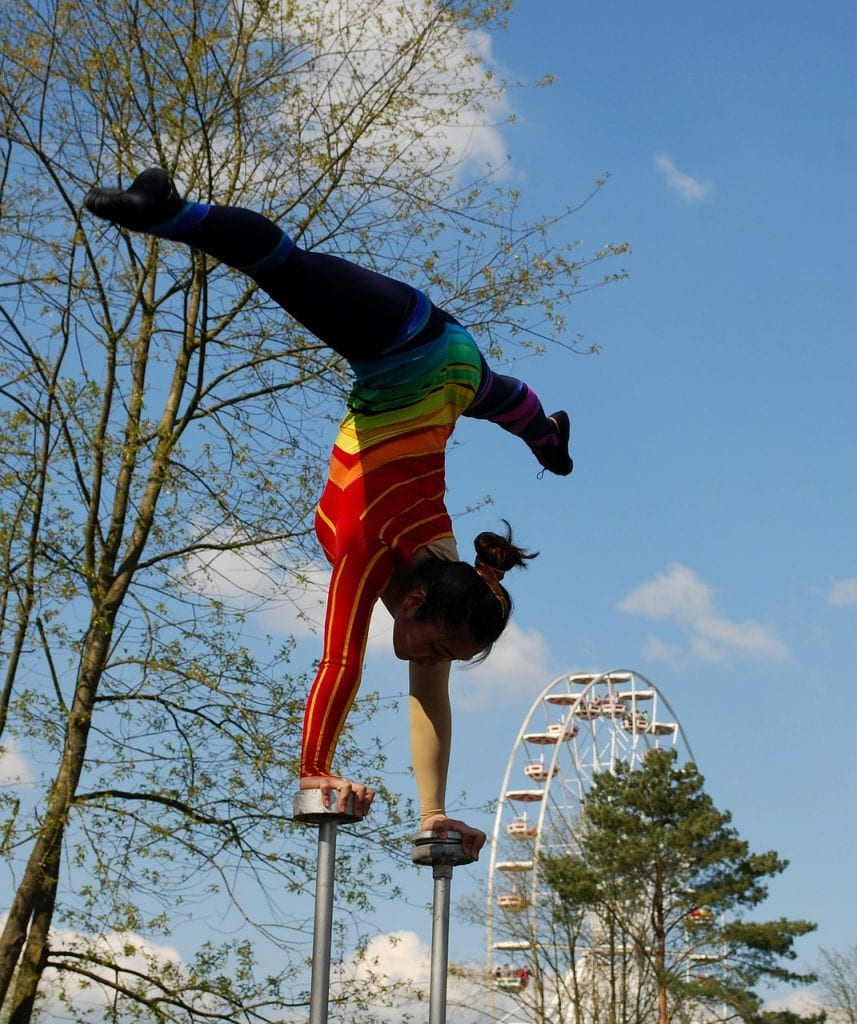 Photo of a circus performer doing handstand on stilts with full side splits.